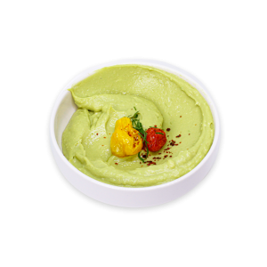 Avocado Hummus garnished with roasted tomatoes in a white bowl