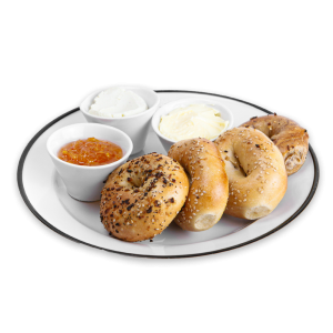 Bagels on a white plate with cream cheese, butter and jelly