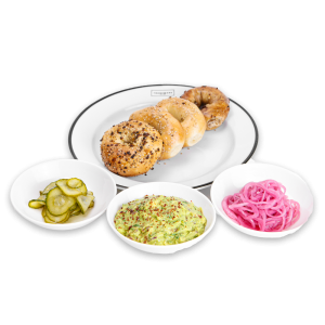 Bagels on a white plate with pickles, guacamole, and onions